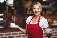 Pretty waitress holding two cups of coffees Stock Photos