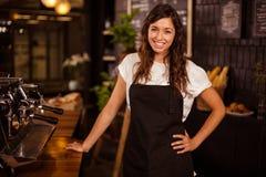 Pretty waitress posing next to coffee machine Stock Images