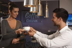 Pretty waitress serving businessman in bar Royalty Free Stock Photo