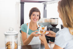Pretty waitress serving muffin to customer Stock Images