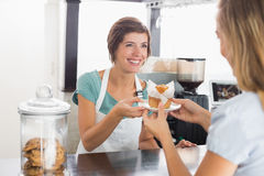 Pretty waitress serving muffin to customer Royalty Free Stock Images