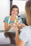 Pretty waitress serving muffin to customer Stock Image