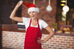 Pretty waitress touching her santa hat Royalty Free Stock Photos