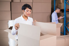 Pretty warehouse manager looking in box Royalty Free Stock Photo