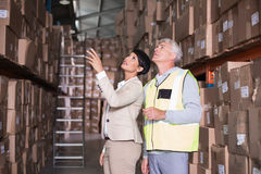 Pretty warehouse manager talking to foreman Stock Image