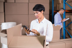 Pretty warehouse manager using calculator Royalty Free Stock Images