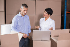 Pretty warehouse manager using laptop with colleague Stock Images