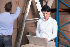 Pretty warehouse manager using laptop Stock Photos