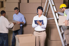 Pretty warehouse manager using tablet during busy period Royalty Free Stock Photography