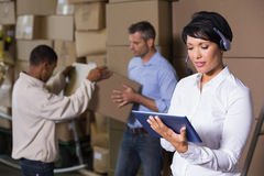 Pretty warehouse manager using tablet during busy period Stock Photo
