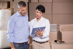 Pretty warehouse manager using tablet pc with colleague Royalty Free Stock Photos