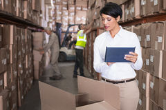 Pretty warehouse manager using tablet pc Royalty Free Stock Image