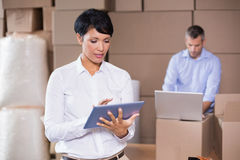 Pretty warehouse manager using tablet pc Stock Photo