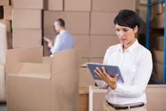Pretty warehouse manager using tablet pc Stock Photography