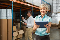 Pretty warehouse manager using tablet pc. In a large warehouse Royalty Free Stock Images