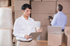 Pretty warehouse manager writing on clipboard Stock Images