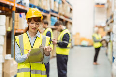 Pretty warehouse manager writing on clipboard Stock Photo