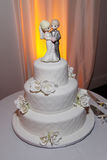 Pretty Wedding Cake- Classy. Three tire white wedding cake with Bride and groom statue on top. Precious Moments topper. White roses decorating sides Stock Images