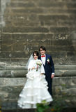 Pretty wedding couple pose on the pass behind an old gray wall.  Stock Photo