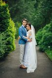 Pretty wedding couple poses in a green spring garden. Hugging newlyweds stand under green branches in the park Stock Image