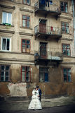 Pretty wedding couple stands under old half-ruined balconies.  Royalty Free Stock Photo