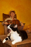 Pretty Western Woman with Guitar and cat. Pretty western woman in antique rocking chair with guitar and cat Stock Images