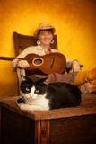 Pretty Western Woman with Guitar and cat. Pretty western woman in antique rocking chair with guitar and cat Royalty Free Stock Photo