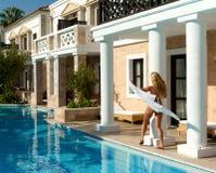 Pretty white bikini girl walking near pool. Greek style royalty free stock photos