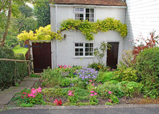 Pretty white brick kent country cottage. Photo of a pretty whitewashed brick kent country cottage with typical cottage plants and flowers growing in a tiered Stock Photo