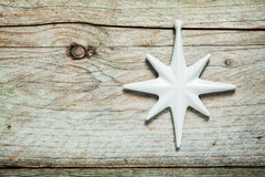 Pretty white Christmas star on old wood. Pretty white Christmas star on old weathered wood with knots and cracks and copyspace for your seasonal message stock photos