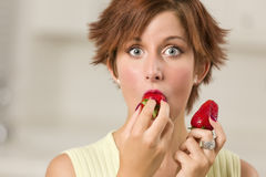 Pretty Wide-eyed Woman Biting Strawberry Stock Image