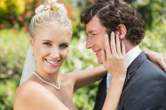 Pretty wife touching her new husbands cheek smiling at camera Stock Image