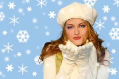 Pretty Winter Girl Blowing Kisses int he Snow. Beautiful Woman Blowing Kisses in the Snow Wearing Scarf and Hat Stock Image