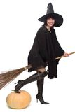 Pretty witch. Bestridden a broom and ready to fly away, with a toe on large pumpkin Royalty Free Stock Image