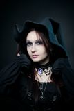 Pretty witch. Posing over dark background Royalty Free Stock Image