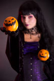 Pretty witch holding Jack o lantern oranges. Selective focus on fruits stock images