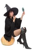 Pretty witch making up. Pretty witch sitting on large pumpkin and making up to prepare for Halloween Royalty Free Stock Photo