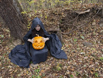 Pretty witch with pumpkin in the forest royalty free stock image