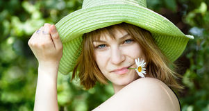 Pretty woman. Young beautiful girl in straw hat with camomile flower royalty free stock images