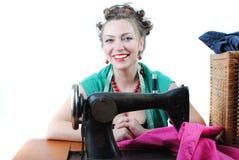 Pretty woman. Using a sewing machine stock image
