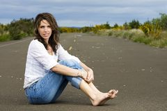 Pretty Woman. A beautiful bare foot woman sitting on an empty road Stock Images