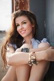 Pretty woman. In blue shirt sitting near a brick wall Stock Photography