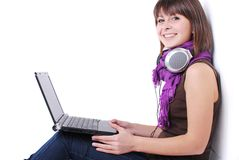 Pretty woman. Happy cute girl listening to music on the laptop sitting against wall with laptop stock image