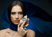 Pretty woman. The very  pretty woman with dark blue neckerchief,  rings with huge blue brilliant, sensual sexuality gaze Royalty Free Stock Images