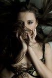 Pretty woman. The very  pretty woman at the wall, dark tousled long hair , blast, sensual strict  gaze Stock Photos