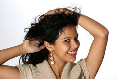 Pretty Woman. Cute young Hispanic woman wearing a beige sweater holding up her long black hair Stock Images