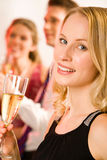 Pretty woman. Portrait of pretty woman holding the glass of champagne on the background of two people royalty free stock image