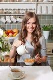 Pretty woman adding milk to cornflakes Stock Photos