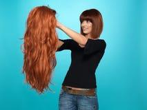Pretty woman admiring long hair wig Royalty Free Stock Photography