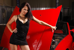 Pretty woman against the car hood. Royalty Free Stock Photography